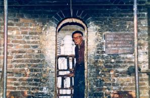 Ο Νίκος Κουρτζής στο φούρνο του. Δεξιά φαίνεται πινακίδα που αναγράφει: ΠΡΟΤΥΠΟΣ ΚΛΙΒΑΝΟΣ ΚΕΡΑΜΙΚΗΣ ΑΝΕΓΕΡΘΕΙΣ ΜΕ ΤΗΝ ΒΟΗΘΕΙΑΝ ΤΟΥ ΕΘΝΙΚΟΥ ΟΡΓΑΝΙΣΜΟΥ ΕΛΛΗΝΙΚΗΣ ΧΕΙΡΟΤΕΧΝΙΑΣ. 1964»