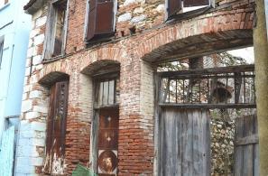 Αψιδωτά υπέρθυρα ερειπωμένων σπιτιών με γυμνή τοιχοποιία.